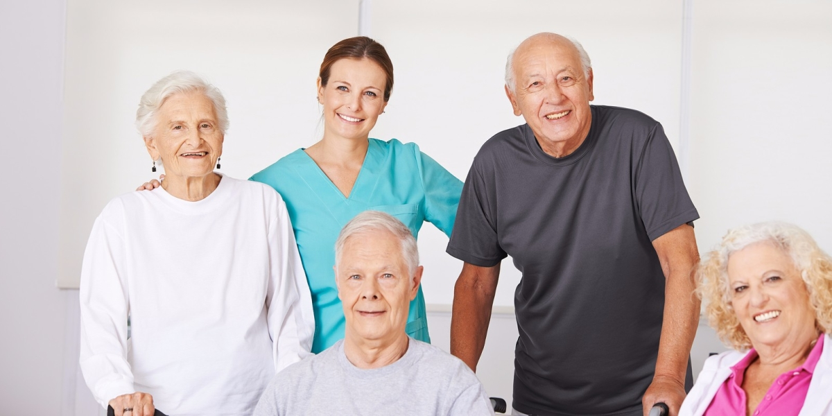 Happy group of senior citizens in nursing home with geriatric nu